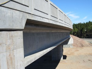 Contrast between straight girders and the curved bridge deck/barriers